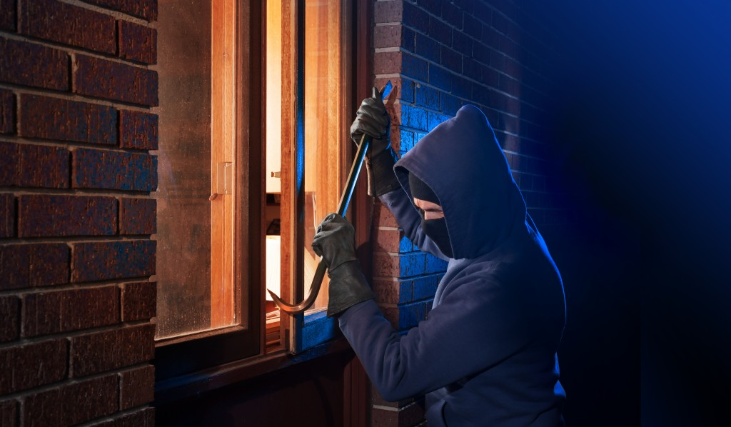 Burglar entering the house through a window