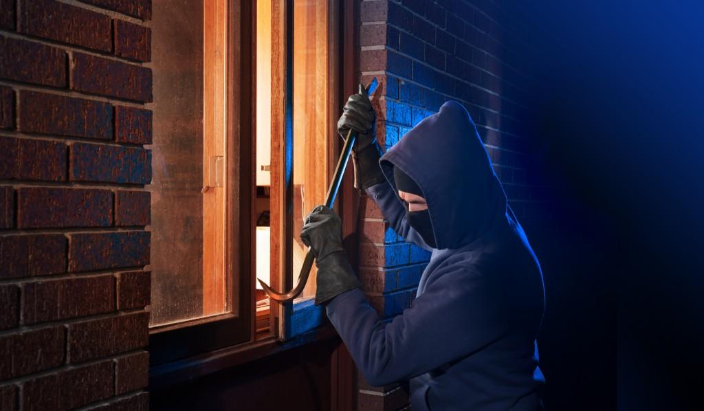Burglar entering the house through a window